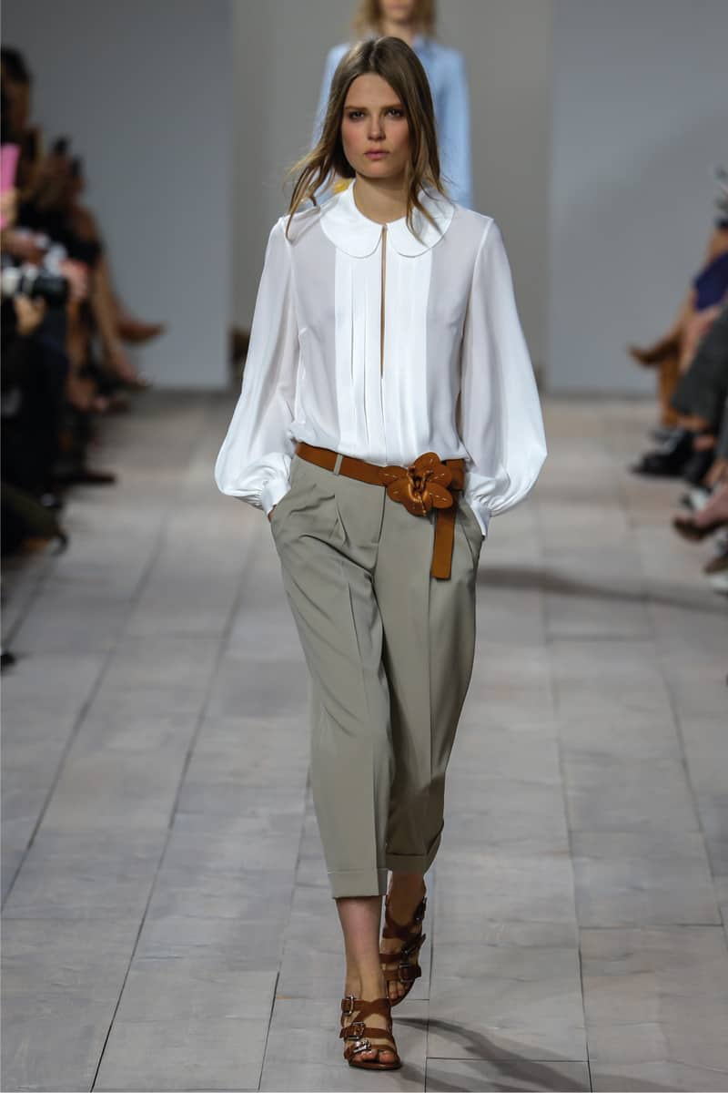 Runway model on a fashion show wearing airy white shirt with relaxed khaki capris and brown strappy belt and shoes