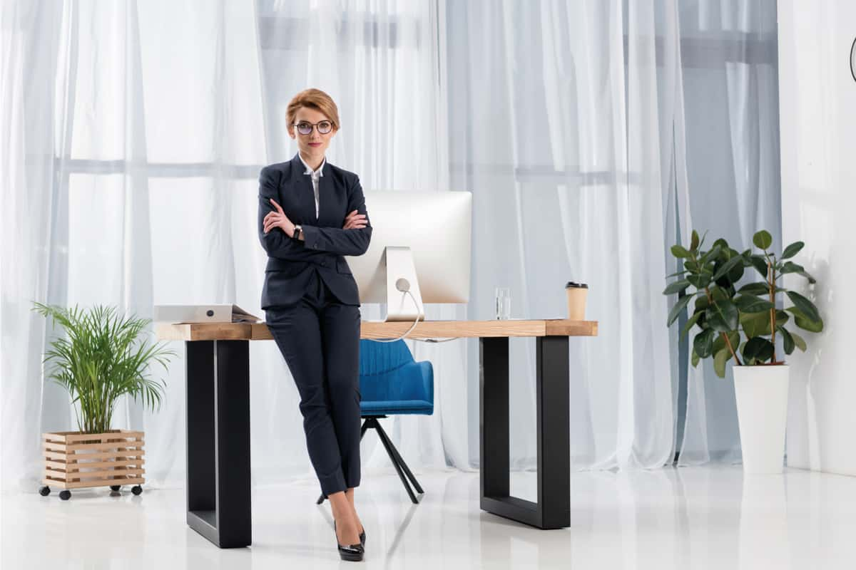 Woman at the office desk wearing a suit with capri trousers and shiny black pumps