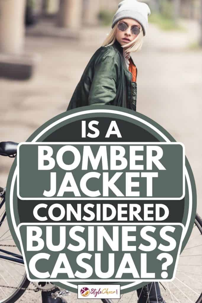 Woman holding a bicycle wearing a green bomber jacket and eyeglasses, Is A Bomber Jacket Considered Business Casual?