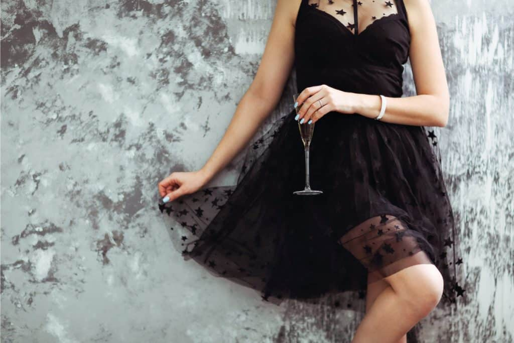 woman in black dress with a glass of champagne, What Color Accessories with Black Dress