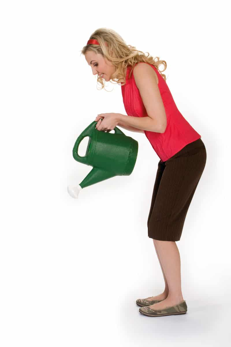 Woman pouring a water can and wearing a pair of flats and a headband with capri pants
