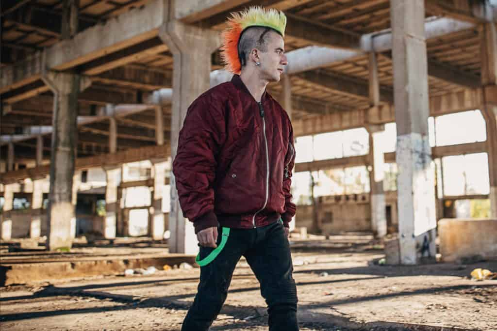 Young male punker with colorful coiffure and red bomber jacket walking in abandoned warehouse, How Much Does A Bomber Jacket Weigh?