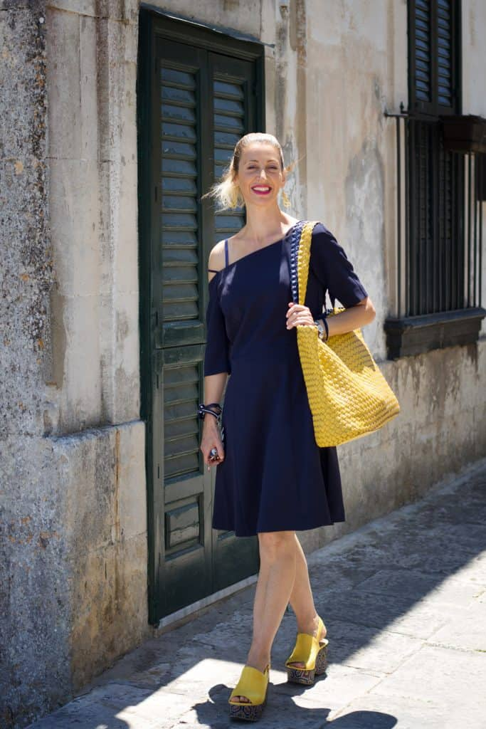 A chic blond sunlit Sicilian woman with an off-shoulder navy blue dress, vibrant yellow bag, and vibrant yellow platform clogs walking down a sidewalk with a typical old building in the background.