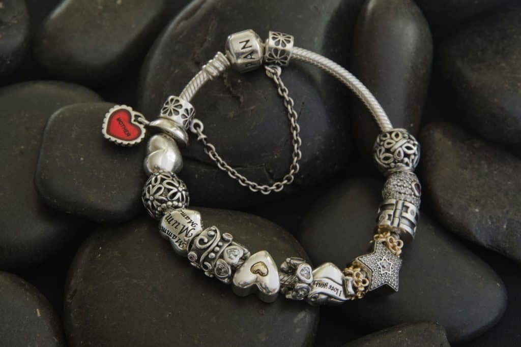 A Pandora bracelet placed on black rocks
