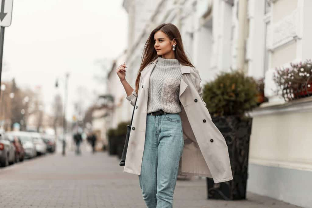 A beautiful woman walking down the street wearing a beige coat and denim pants, What Color Coat Goes With Everything? [5 Great Options With Photos]