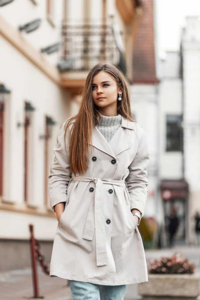 A beautiful woman wearing a long beige colored coat