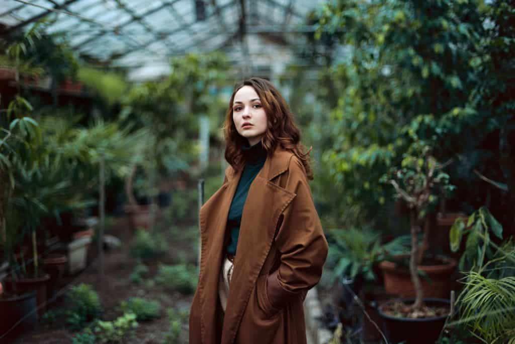 A beautiful woman with dark brown colored hair wearing a brown coat