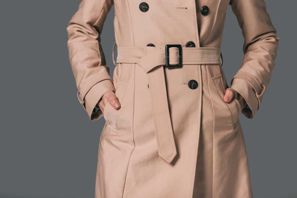 A detailed photo of a woman wearing a beige coat on a gray background
