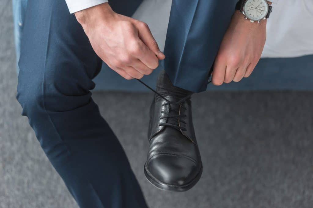 A man tying his black leather shoes
