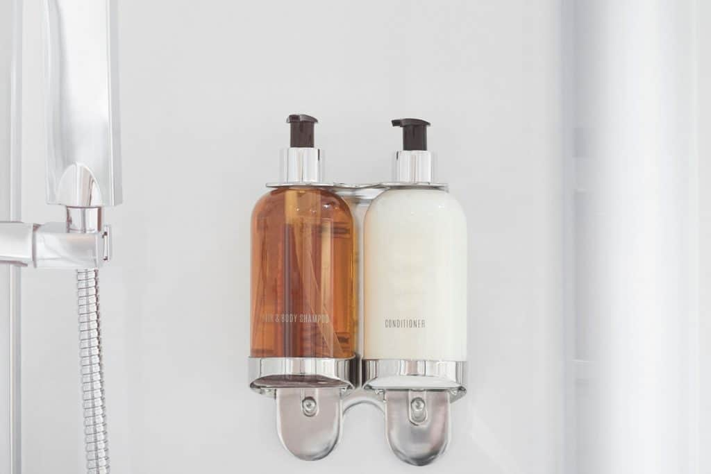 Hair/body shampoo and conditioner bottles inside a modern clean and crisp bathroom