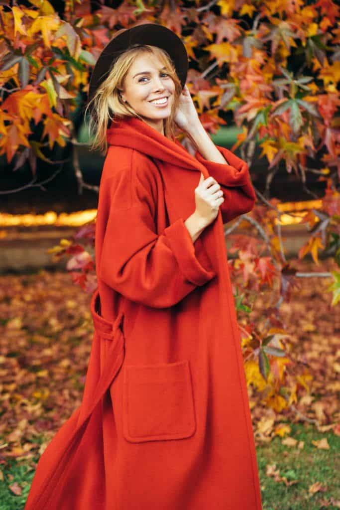 A smiling woman wearing a long red coat and a black sunhat
