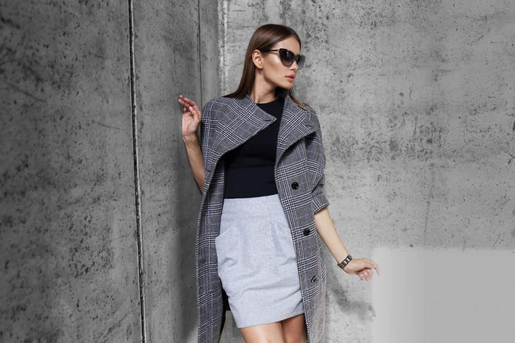 A stylish blonde woman wearing a gray coat, black under shirt, and gray mini skirt