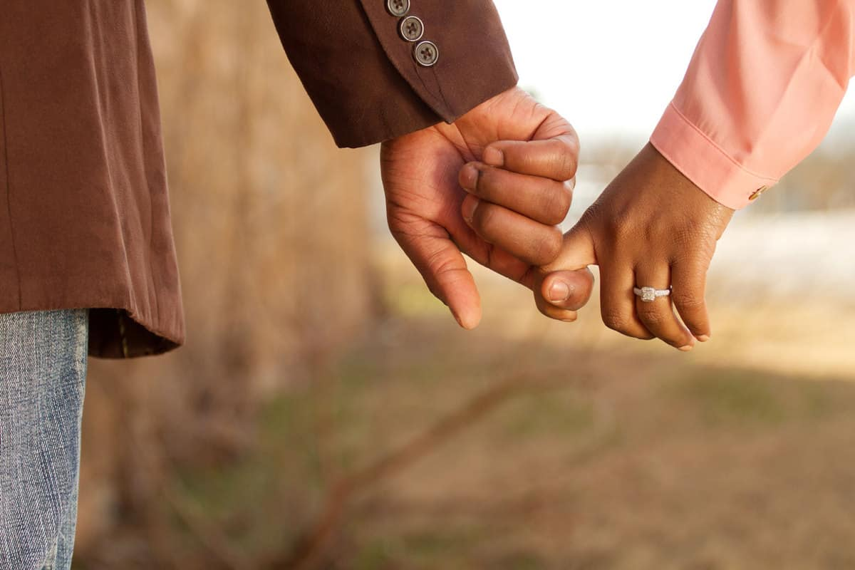 A sweet couple holding hands while walking showing the woman's engagement ring, Can Any Ring Be Used As An Engagement Ring?
