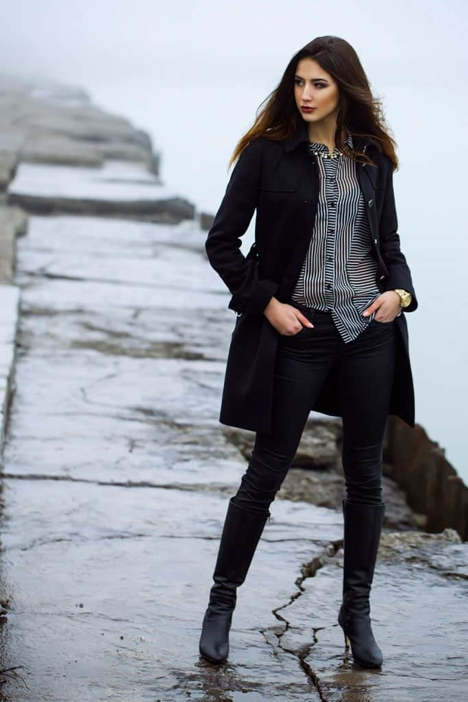 A tall woman wearing a black coat and dark black pants, black boots, and stripped shirt