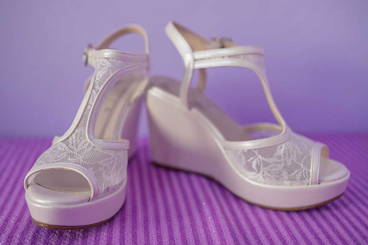 A white platform wedge pumps set against a purple background, Can You Wear Wedge Sandals To A Wedding Or a Black Tie Event?