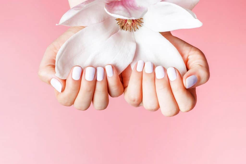 A woman holding a flower while showing her nails polished in white