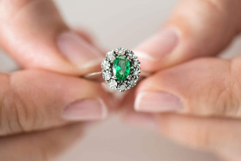 A woman holding an emerald ring encrusted with diamonds on the side