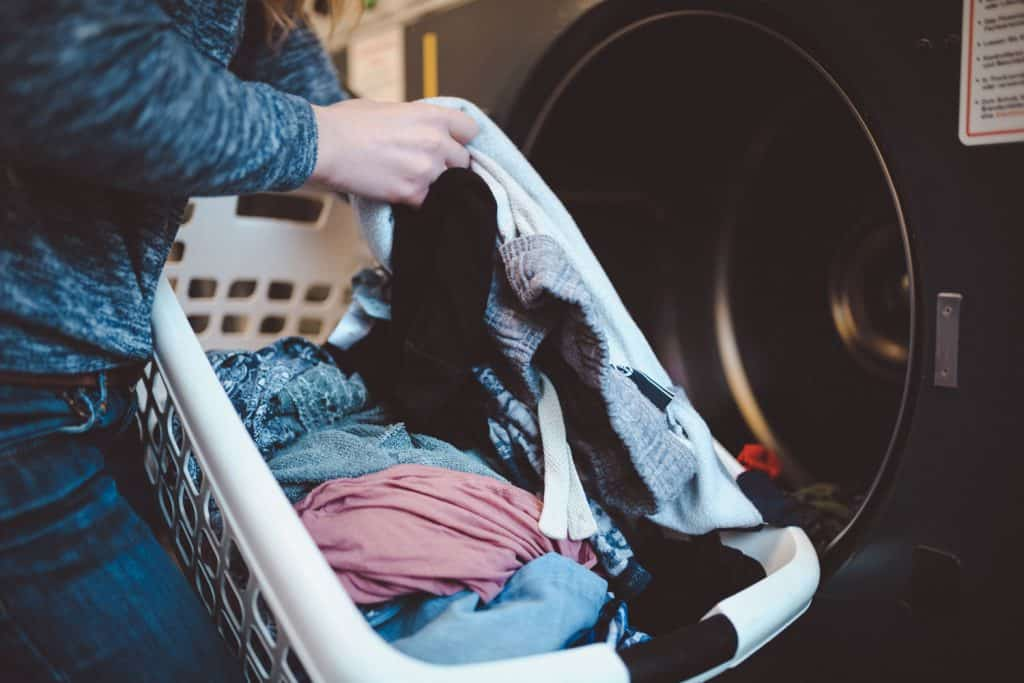 A woman putting laundry inside the washing machine