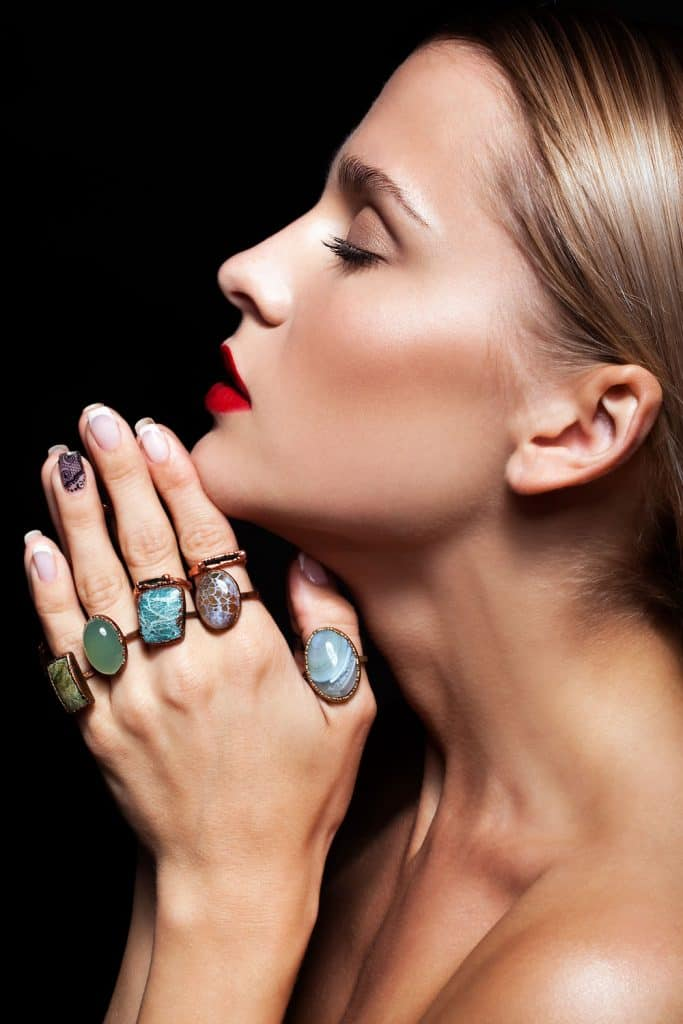 A woman showing different jewelries on her fingers