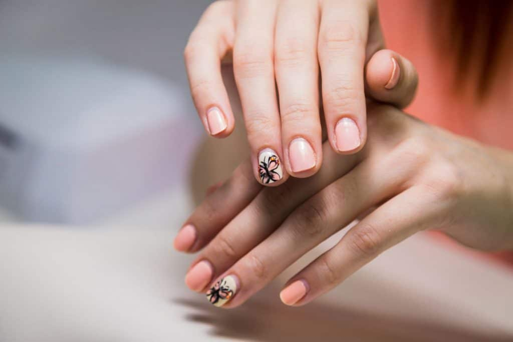 A woman showing her shellac pedicure under the light, Do You Need Long Nails For Shellac (And Do They Add Length?)