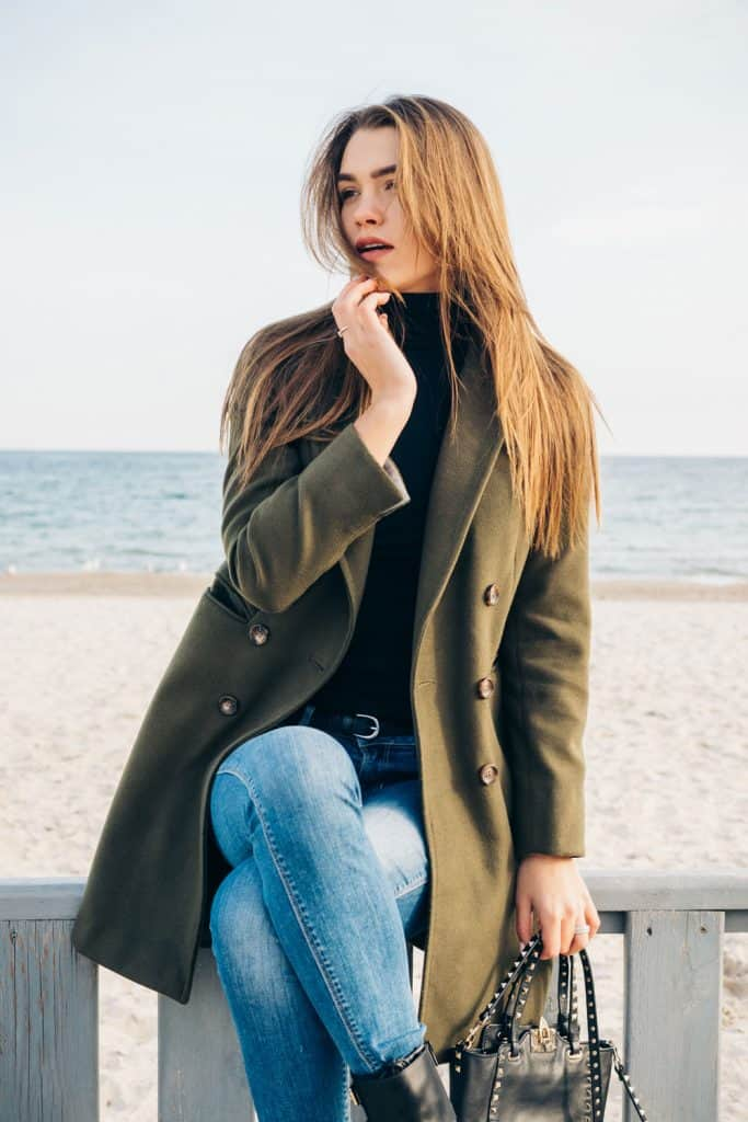 A woman sitting on a fence wearing a dark green coat and denim pants