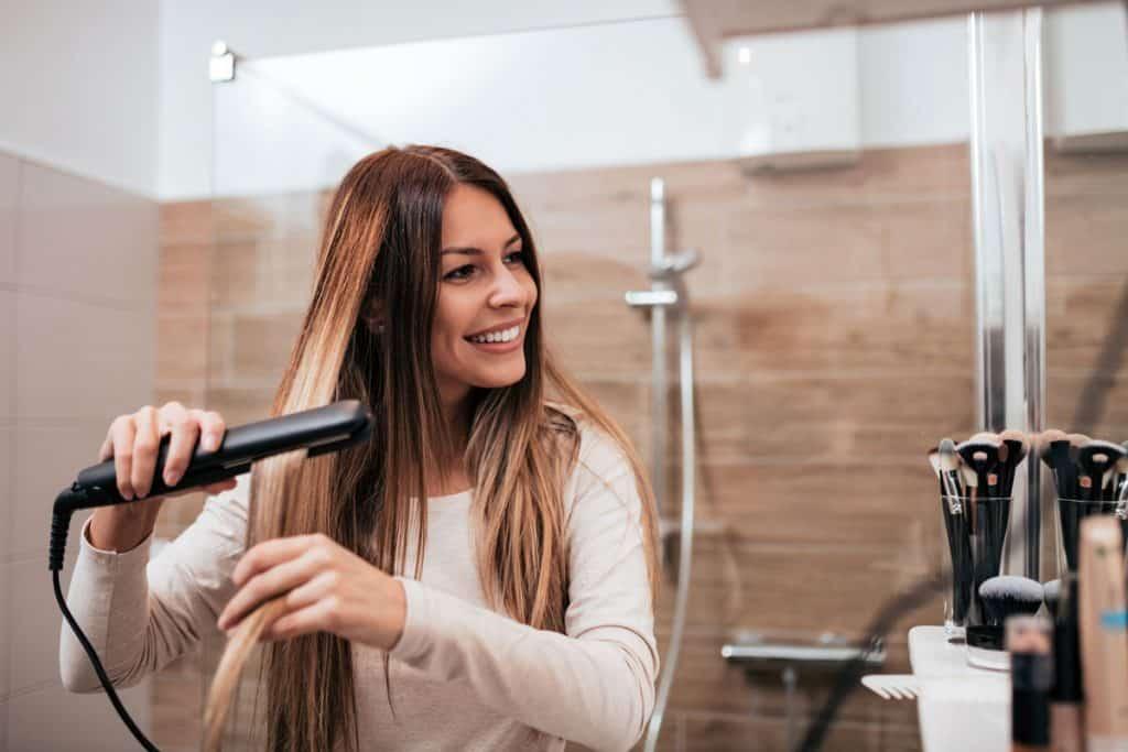 A woman straightening her hair using a hair straightener inside her bathroom, 8 Types Of Hair Straighteners