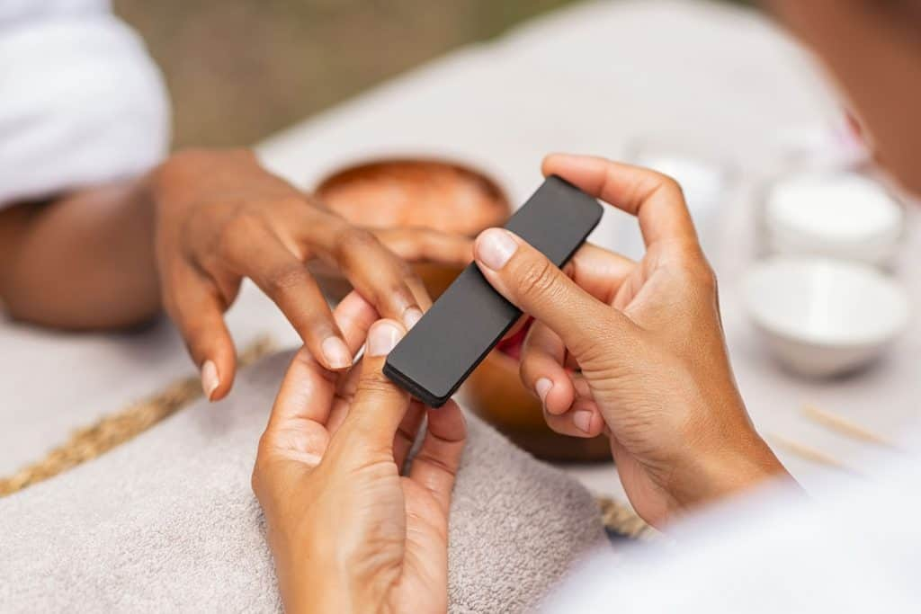 A woman using a buffer on her clients ails