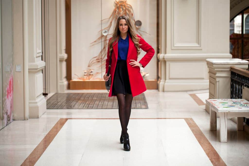A woman wearing a red coat, black mini skirt, blue shirt, and black stockings