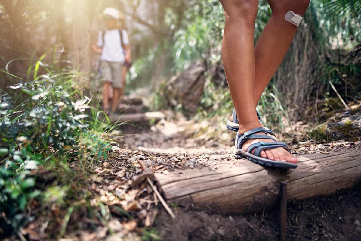 A woman wearing sandals while hiking down a steep hill, How To Stop Sandals From Making Suction Noise