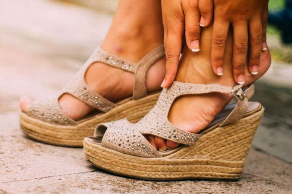 A young woman with wedge sandals sitting on a bench checking her feet, Can You Wear Wedge Sandals In The Fall Or Winter?