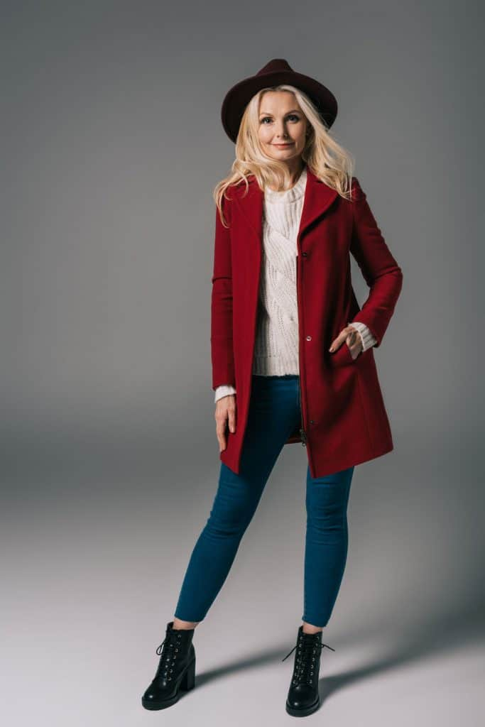 An elderly woman wearing a red coat, black sun hat, black high heeled boots, and denim pants
