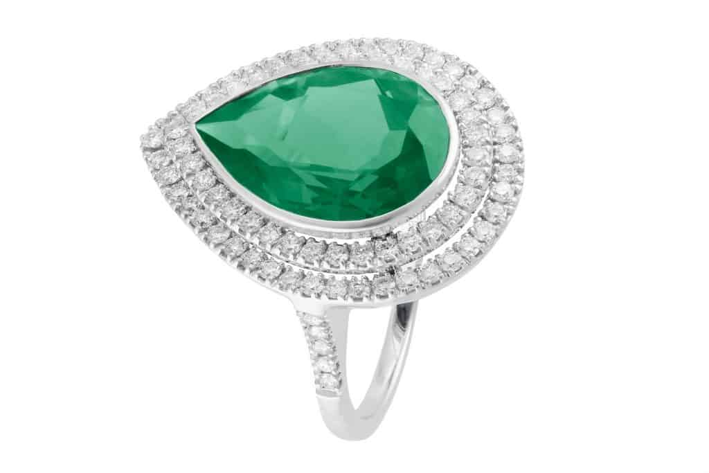 An emerald pear shaped ring encrusted with diamonds on the sides