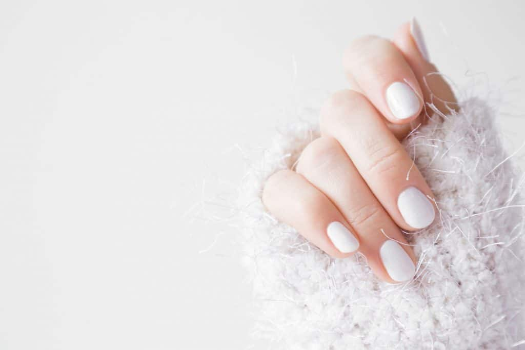 Beautiful groomed woman's hands with white nails on the light gray background, Can You Paint Over Shellac Nails?
