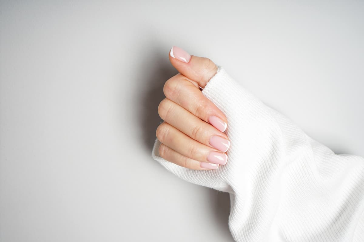 Beautiful hand of a young girl with beautiful manicure on a gray background