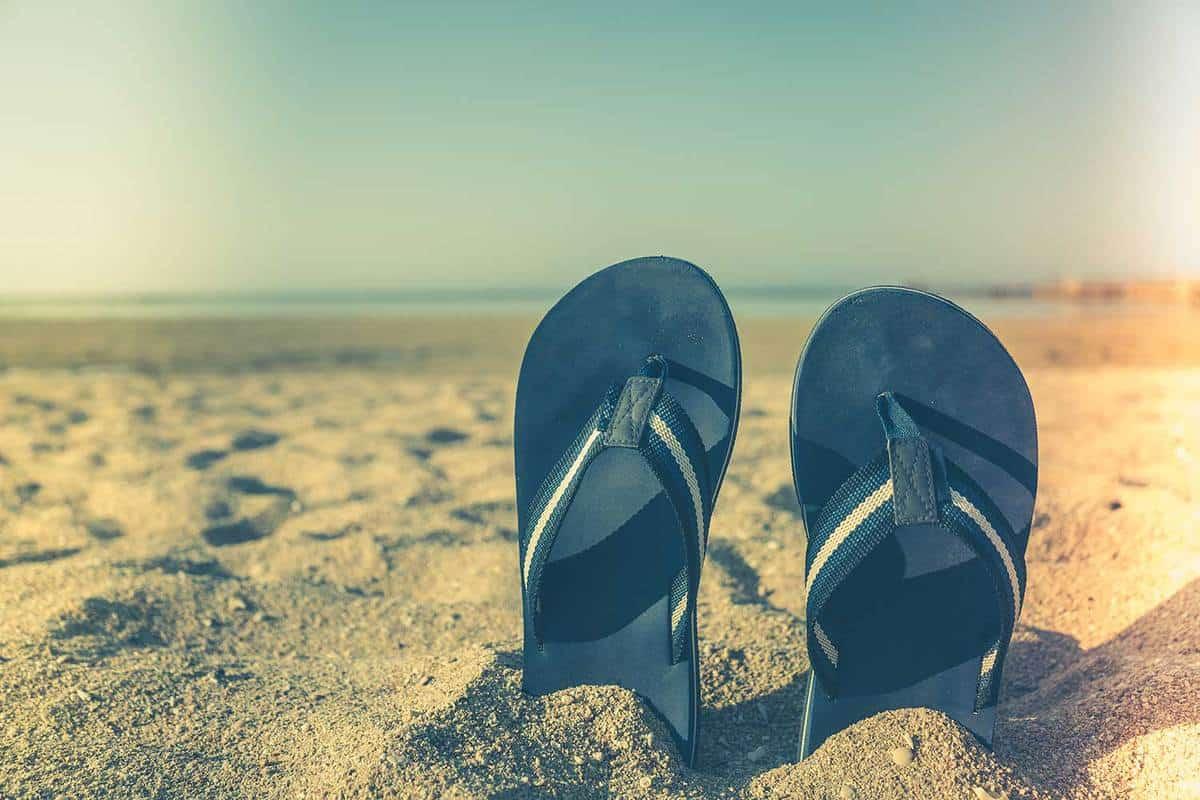 Blue sandal flip flop on yellow sand, How Long Do Rainbow Sandals Last?