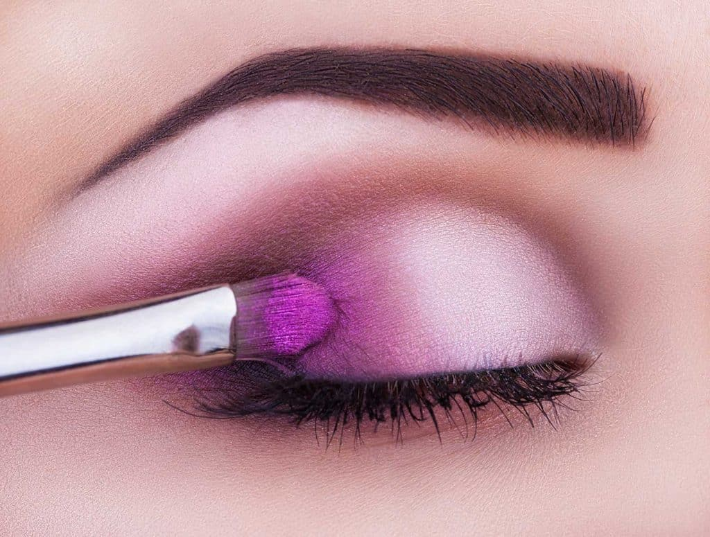Close up of eye makeup woman applying eyeshadow powder