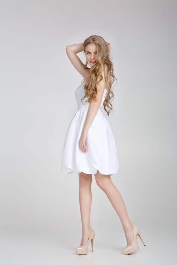 Gorgeous blonde woman wearing white dress and nude shoes