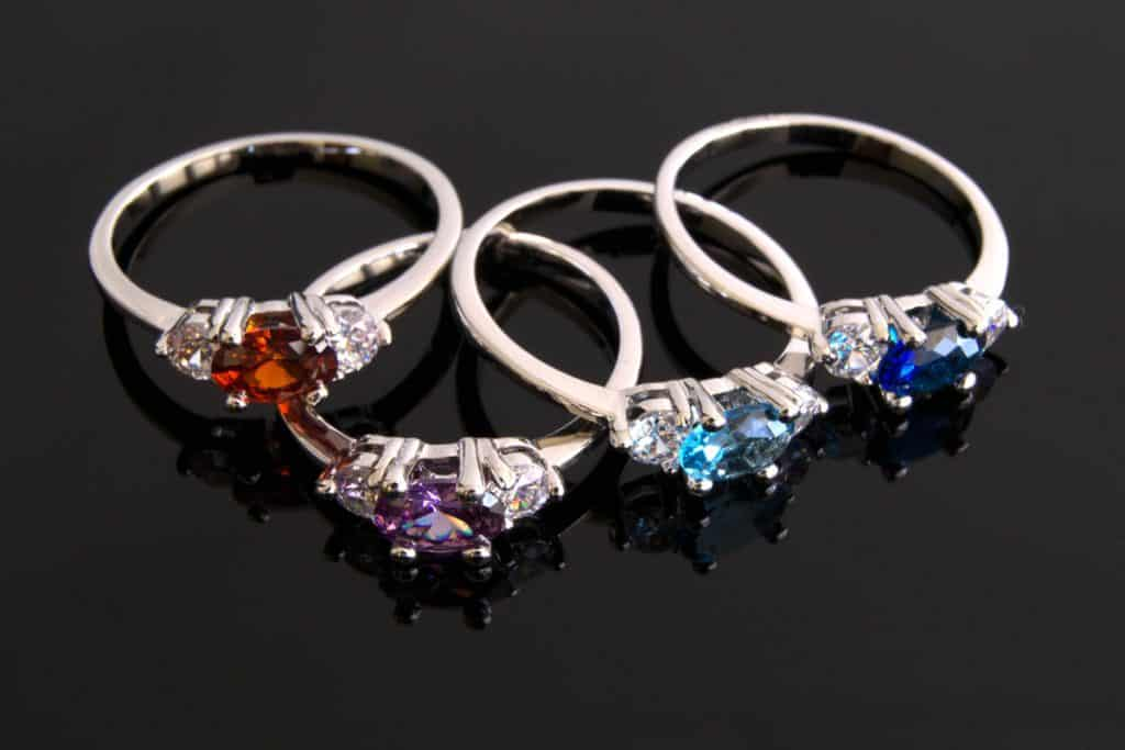 Different colored birthstone rings on a dark gray background, Which Hand Do You Wear A Birthstone Ring On?