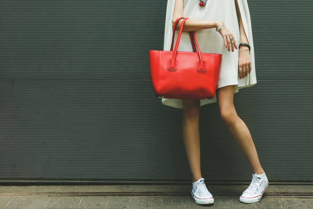 Fashionable beautiful big red handbag on the arm of the girl in a fashionable white dress and sneakers, posing near the wall on a warm summer night, What Color Shoes With a White Dress? [5 Awesome Options!]