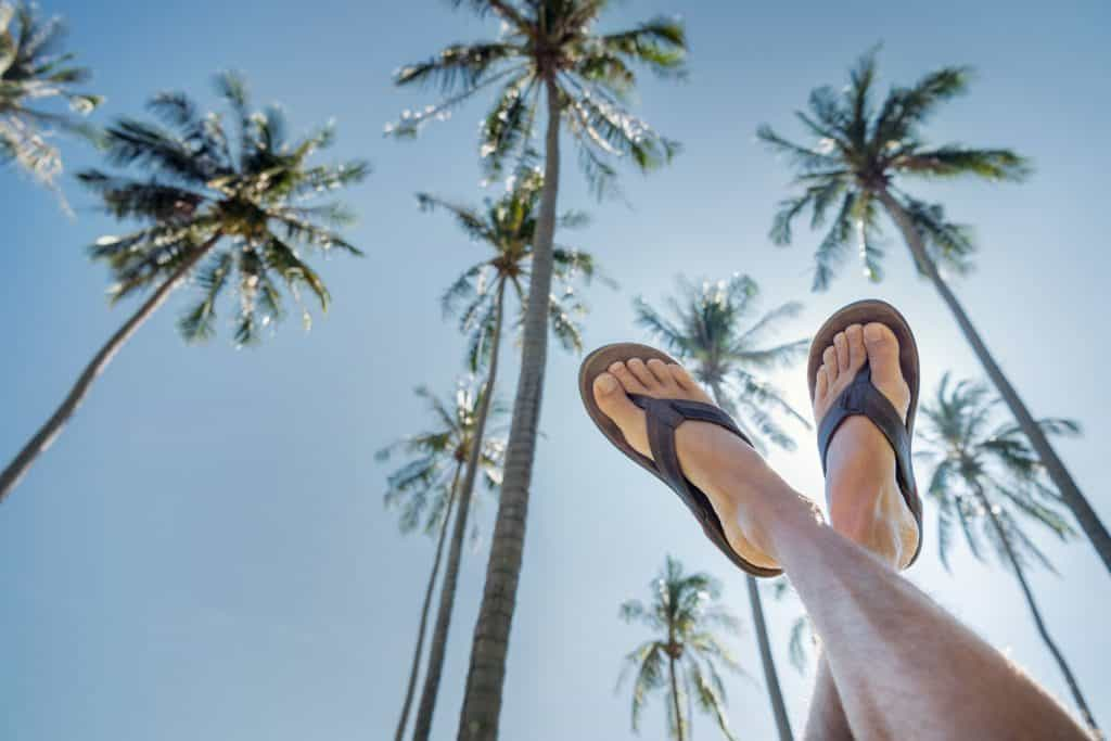 Feet pointing up the clear tropical blue sky with a wonderful palm tree background