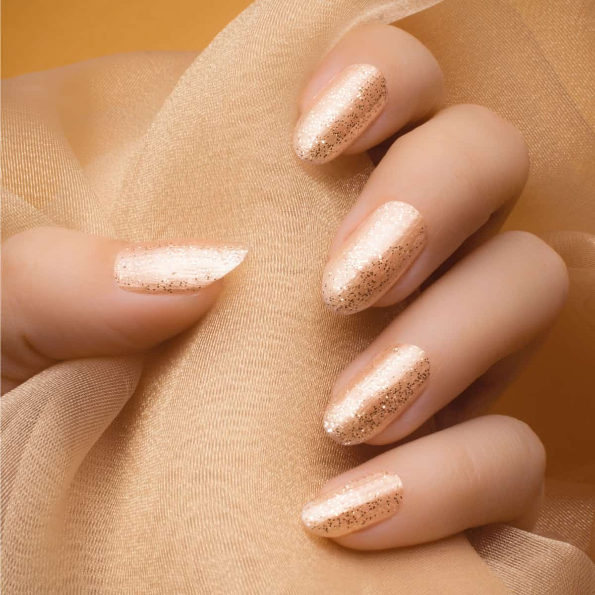 Female hand with glittered beige nails holding a beige textile