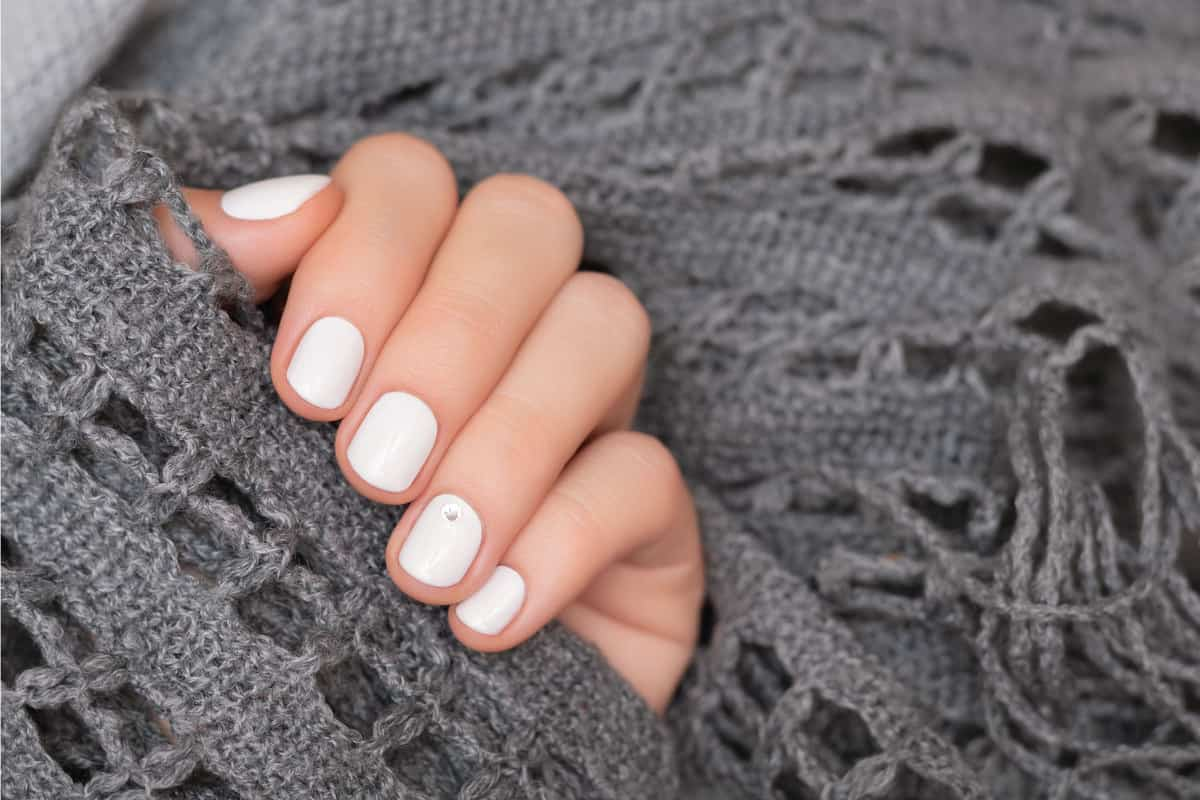 Female hand with white nail design