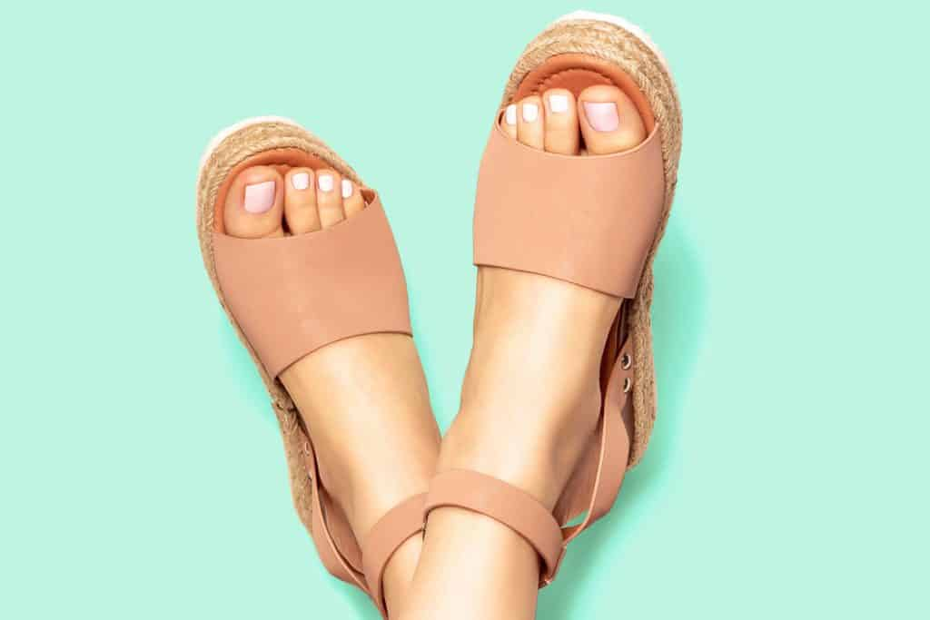 Female feet with white pedicure in summer brown sandals on mint green background