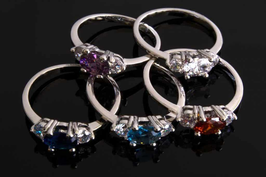 Five birthstone rings with aquamarine, amethyst, sapphire, diamond and ruby stones on black background, How To Clean Birthstone Ring [4 Steps]