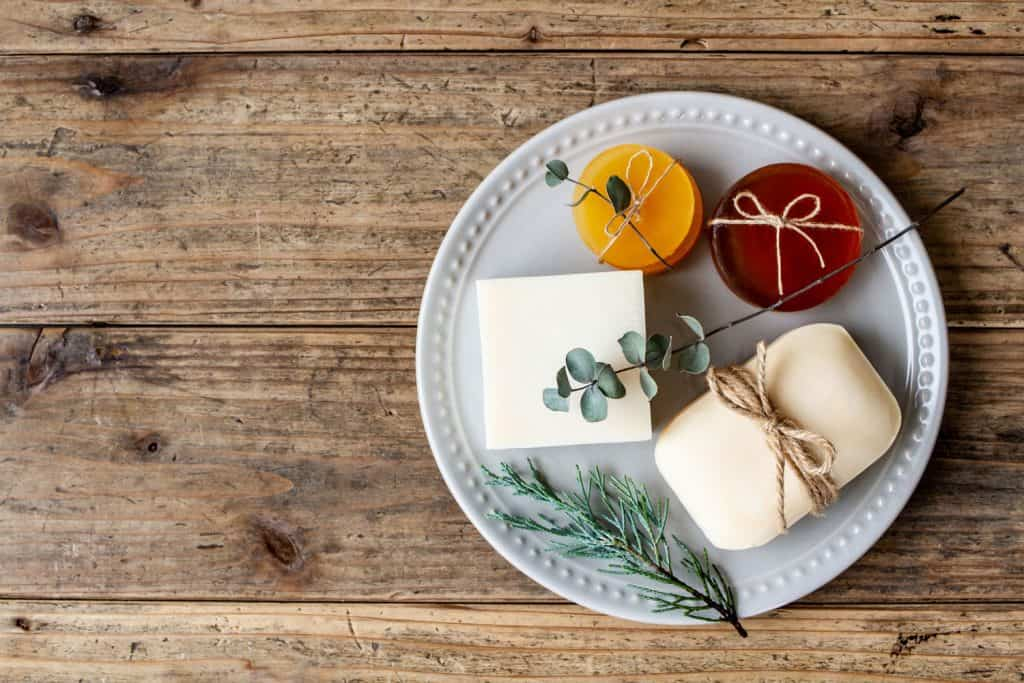 Image of natural bar soap and a wooden table, How To Make Shower Gel From Bar Soap