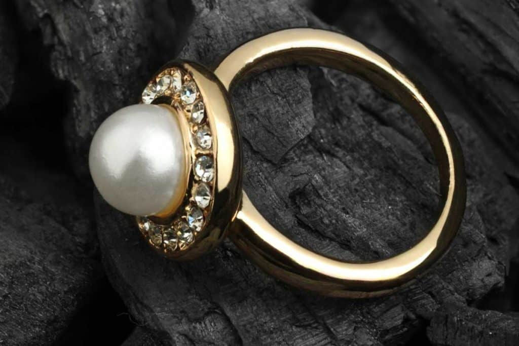 Jewelry ring with diamond and pearl on black coal background, Which Finger To Wear Pearl Ring?