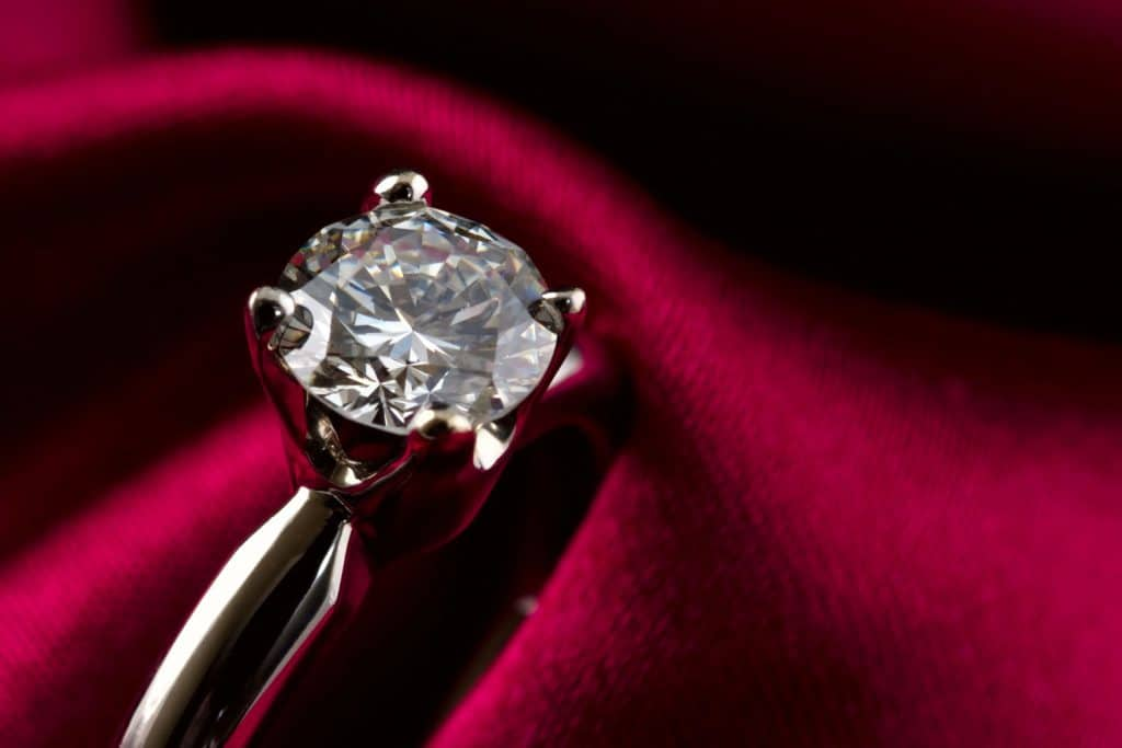 Macro shot of an engagement solitaire diamond ring. Burgundy silk background, Do Engagement Rings Have To Be Diamond?