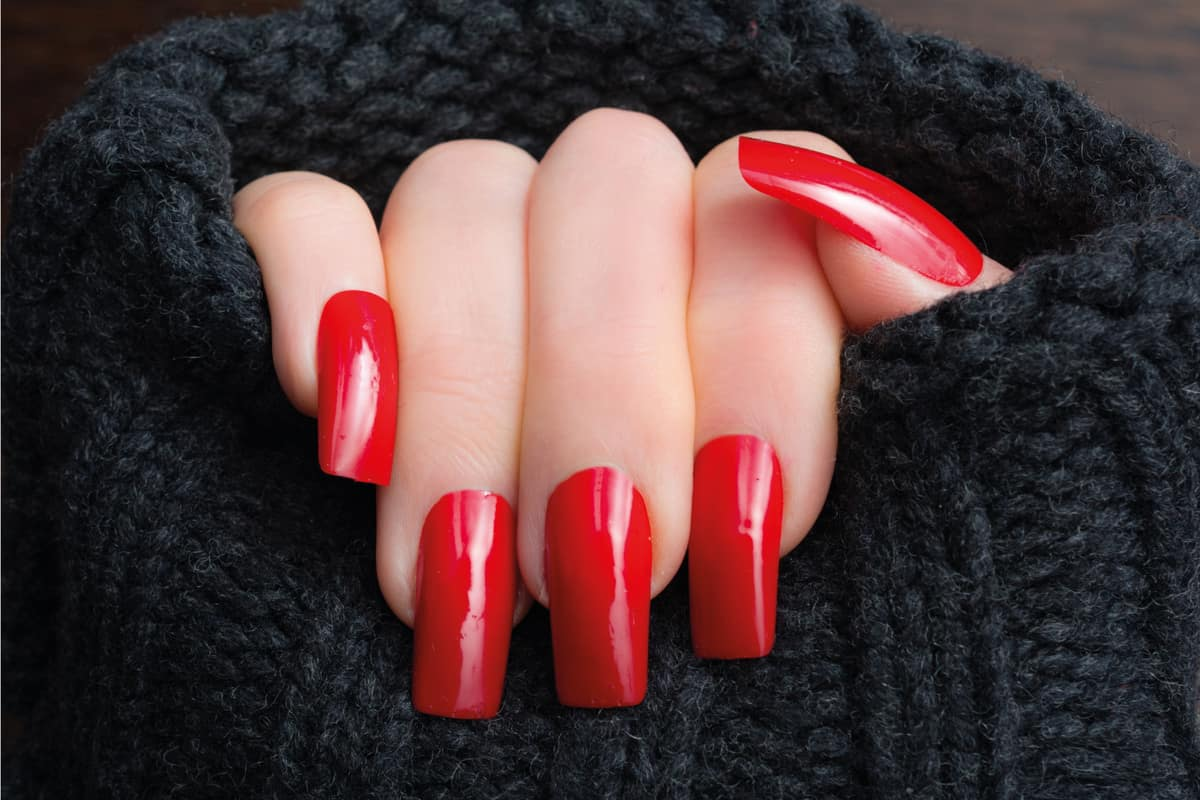 Mature woman showing off her new warm red manicure and dark gray wool sweater