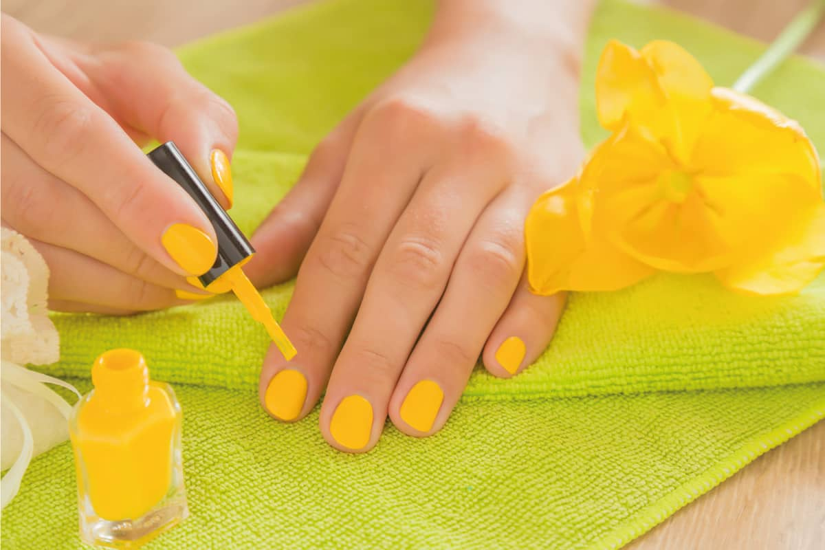 Woman in yellow color nails on a green towel