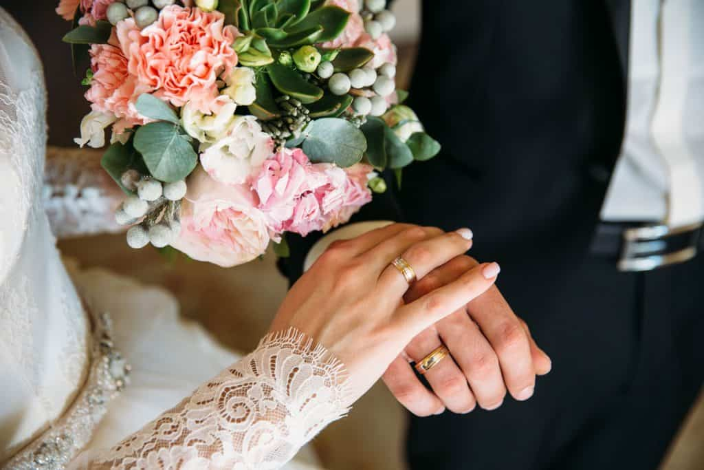 Newly wed couple holding hands showing their engagement rings on their hands, Do You Wear Engagement Ring To Wedding?